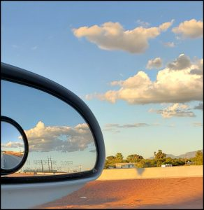 Sunset clouds in the car's rearview mirror
