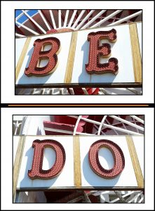 "The words ""be"" and ""do"" on neon signs"