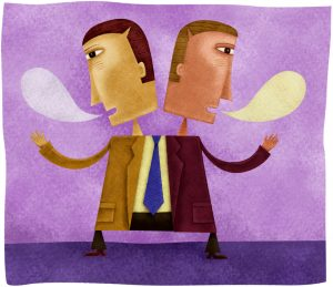 Cartoon of two-headed man in business suit, each head speaking - a thought bubble coming from their mouths, left blank for us to fill in what we think they're saying. All to indicate one person saying two different things at once.
