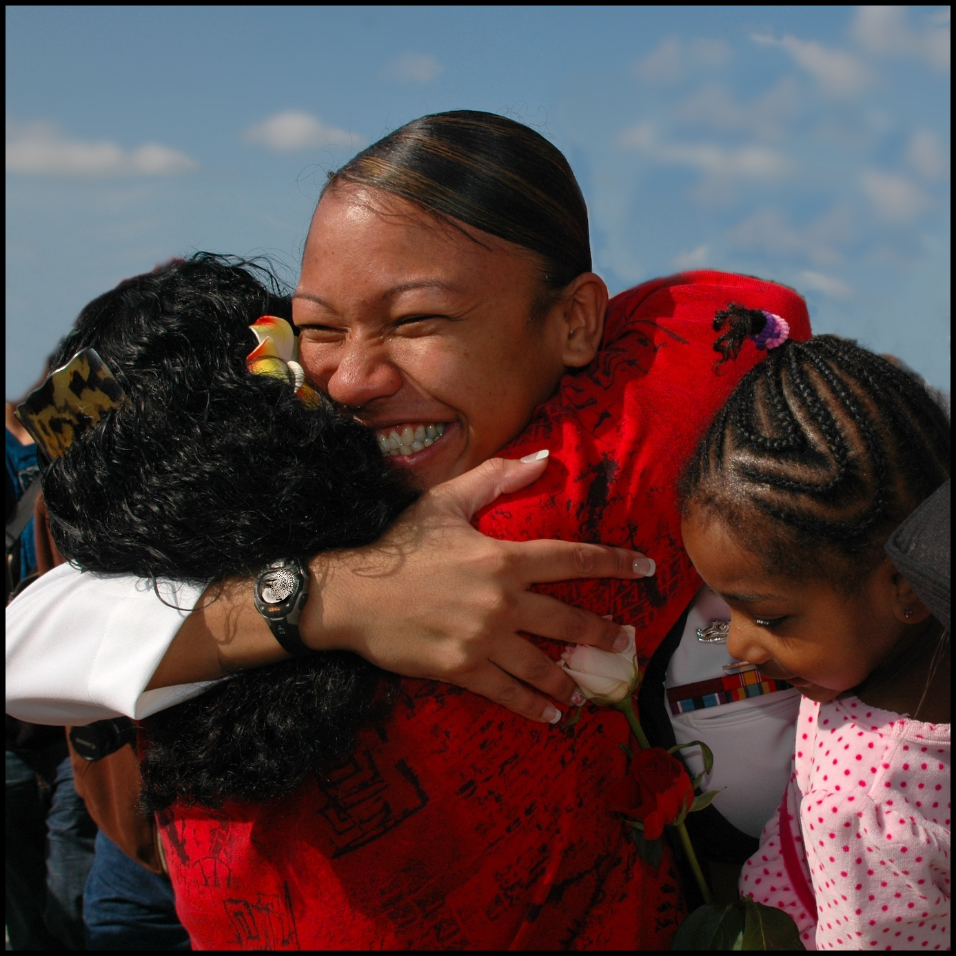 A sailor on leave hugs her children, seeing them for the first time. She has a huge smile on her face.