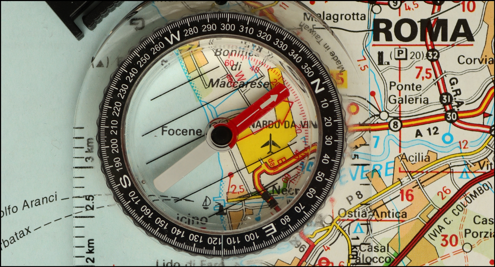 Compass pointing north, resting on a map of Italy, pointing towards Rome