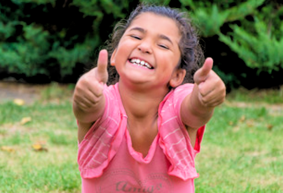 Happy little girl with a pink shirt, pointing at you, grinning so big her teeth are showing