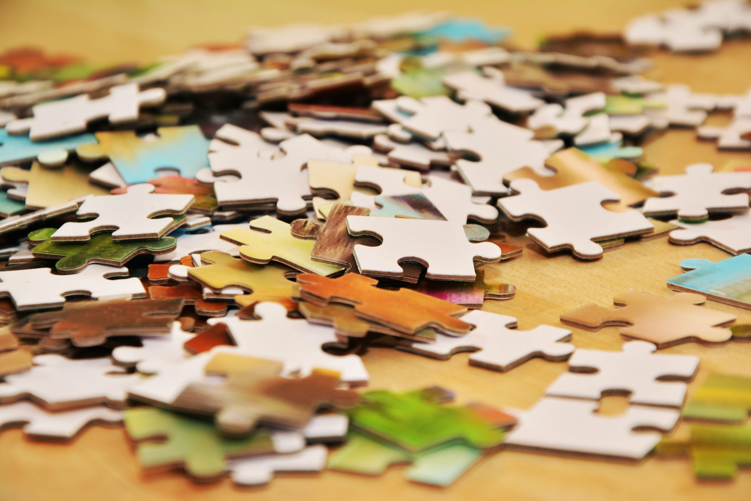Different colored puzzle pieces scattered on a tabletop