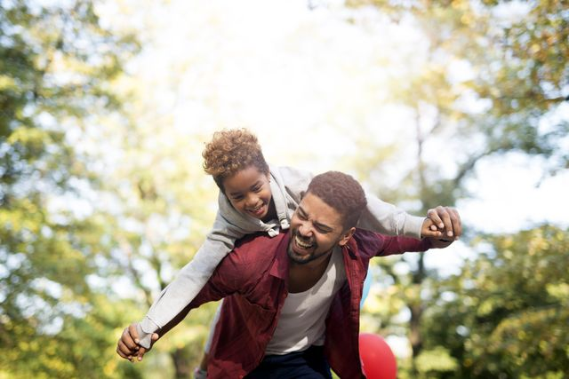 Father holding his daughter on shoulders and laughing