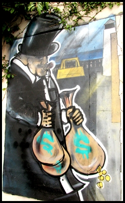 Caricature of an 1800's rich white man carrying sacks of money, painted as part of a mural