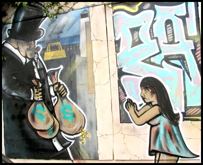 Mural on a building, old fashioned money baron in top hat and tails, carrying bags of money, while a little girl begs him for help