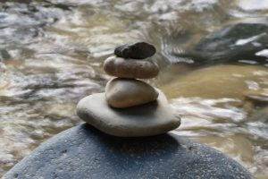 A cairn (stack of stones) sitting in front of a running river. Cairn is steady, river is flowing.