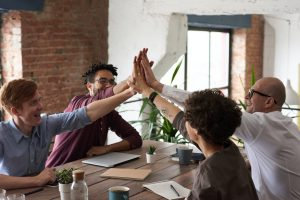 Office team high-fiving around a work table