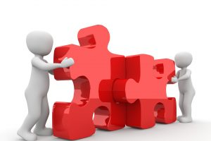 Two cartoon figures, each holding a red puzzle piece, coming together to make them fit